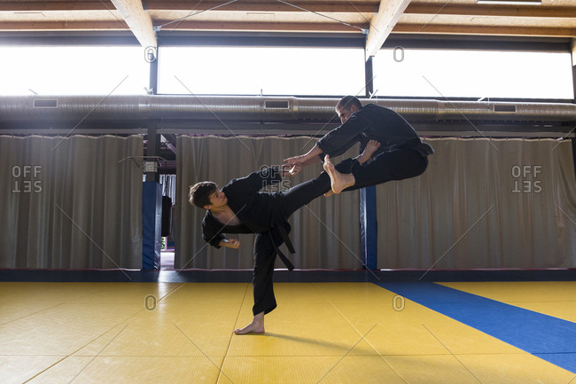 Side view of two fighters in kimonos practicing hapkido and fighting.