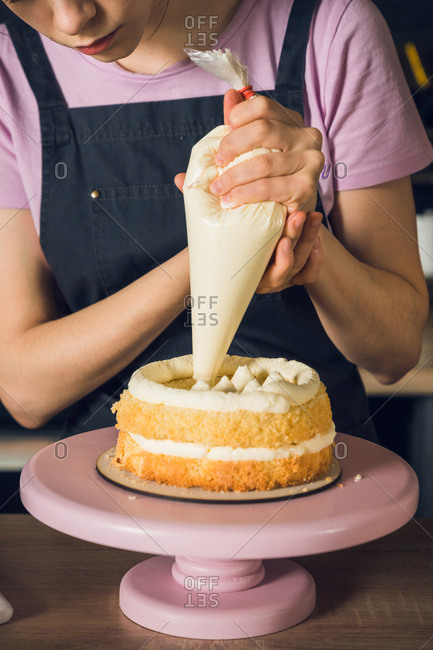 Woman's hands in black apron decorate cake, squeezes out vanilla cream on a top