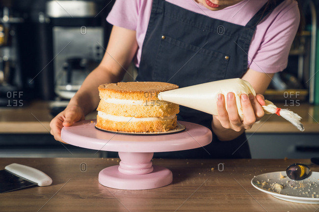 Woman's hands in black apron decorate cake, squeezes out vanilla cream on a side of a cake