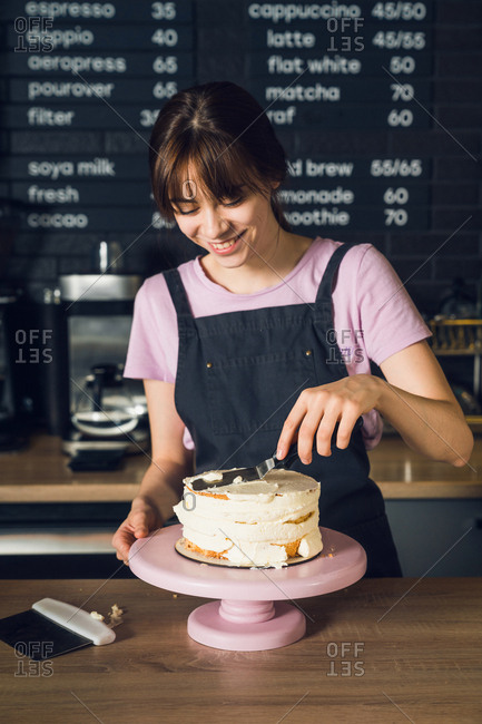 Young woman in dark apron and pink t-shirt smoothing cream on a top of cake by spatula in the cafeteria.