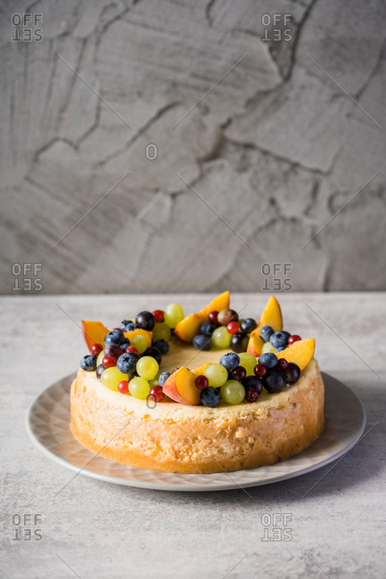 Cake decorated by peach and berries on a grey table.