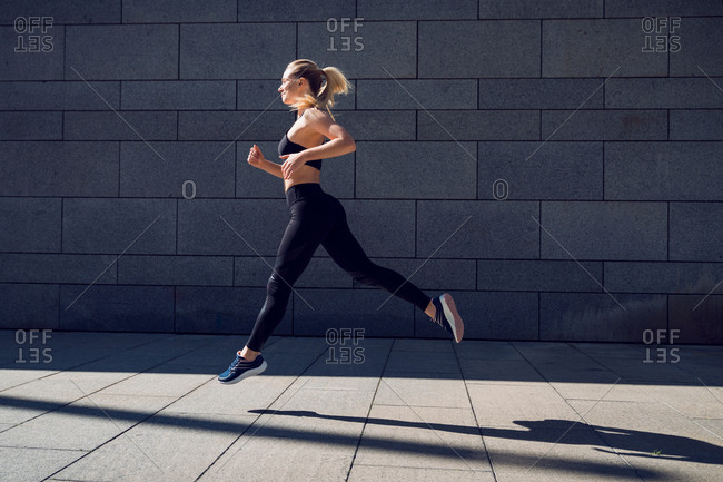 Woman in black sportswear training jumping outdoors in a sun light ray