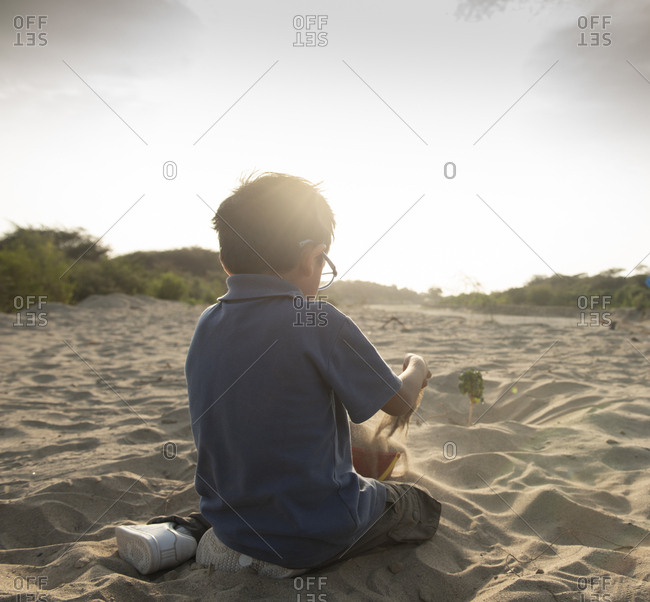 Child plays with sand at sunset in summer