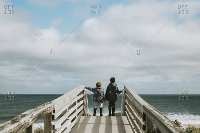 Two boys on boardwalk leading to beach against ocean and cloudy sky
