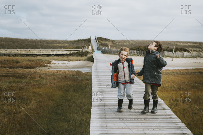 Two windswept brothers on boardwalk over salt marsh and sand dunes