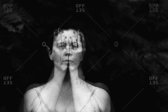 Double exposure portrait of a female behind hands