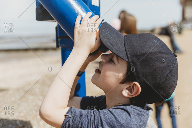 Boy wearing cap looking through telescope at  beach
