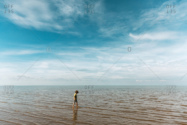 Boy walking in calm ocean against cloudy sky
