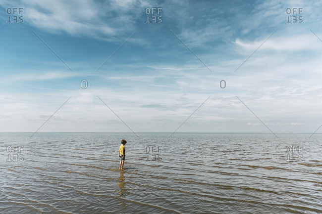 Boy standing in calm ocean against a cloudy sky
