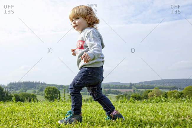 a little boy having fun on a green field in the country side, Caurel Brittany, France.