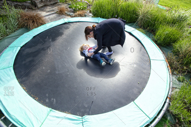 little boy and his mom playing on a trampoline in the country side, Caurel Brittany, France.