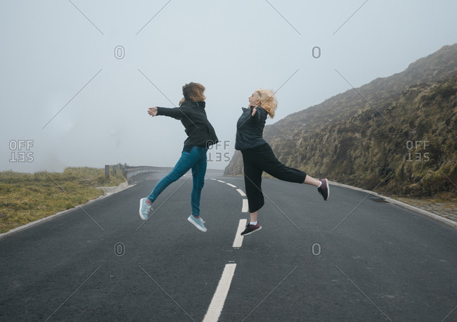 Two young women jumping on a road with fog