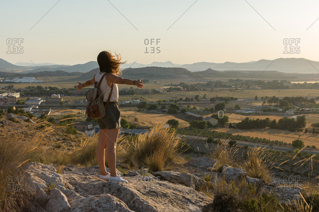 Young woman is raising her arms on top of a mountain