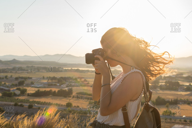 Young woman is taking a photo with her camera on top of a mountain