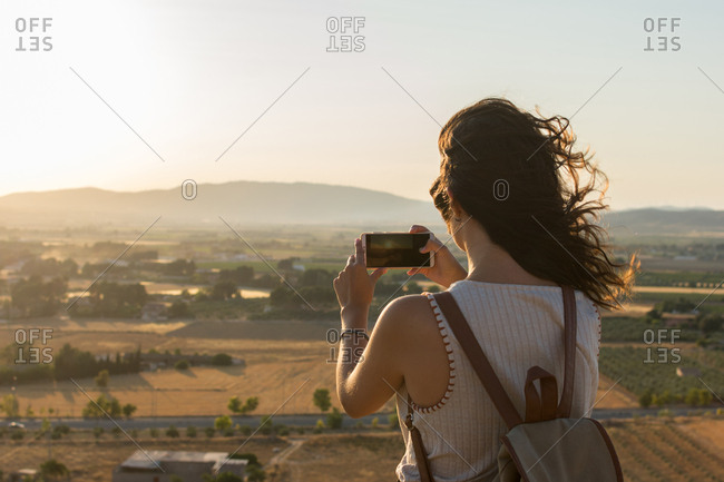 Young woman is taking a photo with her smartphone on top of a mountain