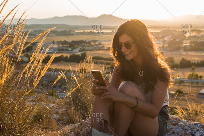 Young woman is watching her smartphone on top of a mountain