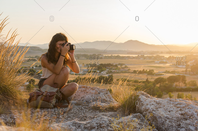 Young woman is taking a picture with her camera on top of a mountain