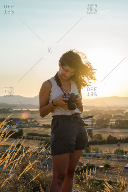 Young woman is watching her pictures in her camera on top of a mountain