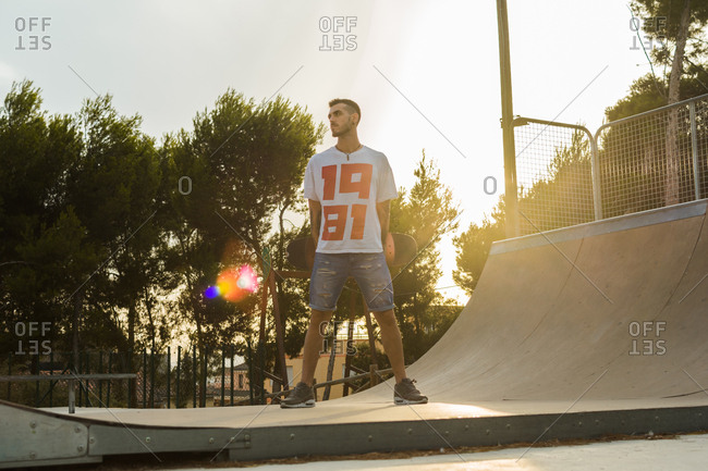 Young man is on a skate court with his skateboard