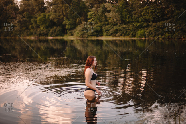 Young woman in a bikini standing in lake in forest