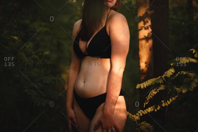 Seductive woman in a bikini standing in forest