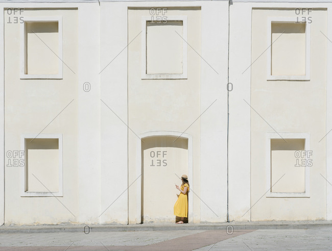 Side view of woman using mobile phone while standing by building in city