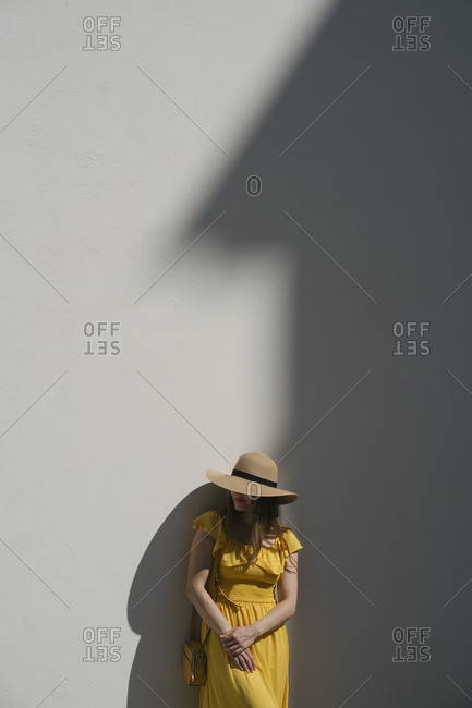 Female tourist wearing hat standing against wall in city