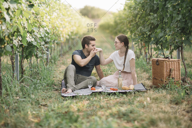 Young couple in love having picnic in the vineyards