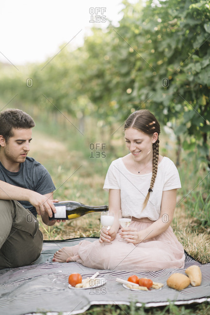 Happy young couple having picnic with Prosecco in the vineyards