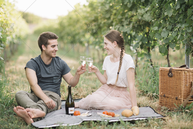 Happy young couple having picnic in the vineyards- toasting with Prosecco