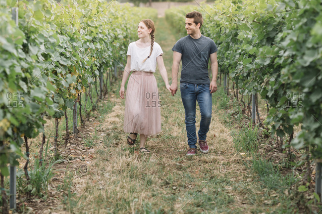 Happy young couple walking hand in hand in the vineyards