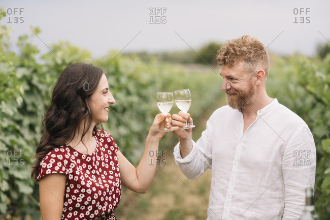 Couple toasting with white wine in the vineyards
