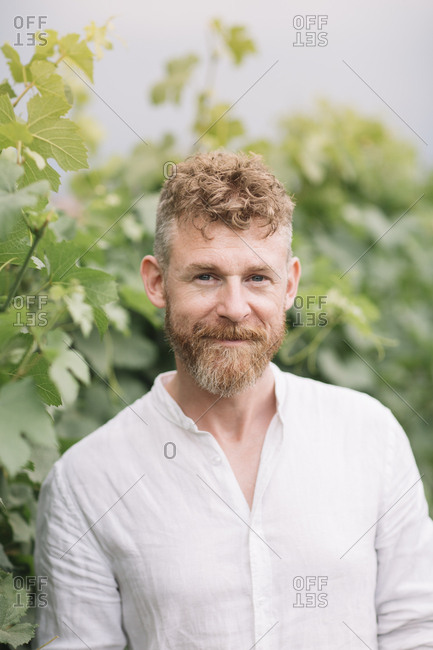 Portrait of bearded man in front of grapevine