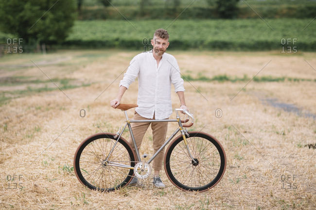 Man with handcrafted racing cycle on stubble field