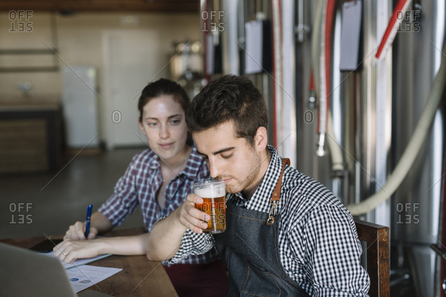 Young entrepreneurs working at a brewery testing beer