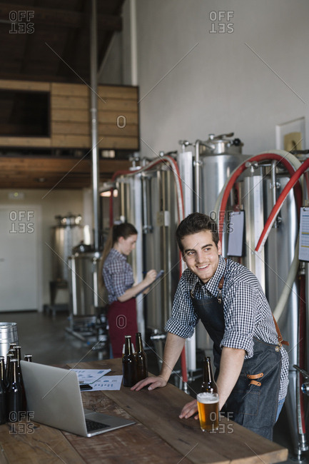 Smiling young entrepreneur working at a brewery