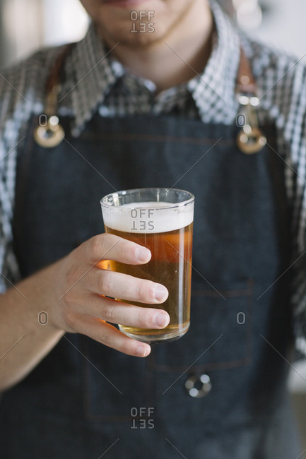 Close-up of young man holding beer glass at a brewery
