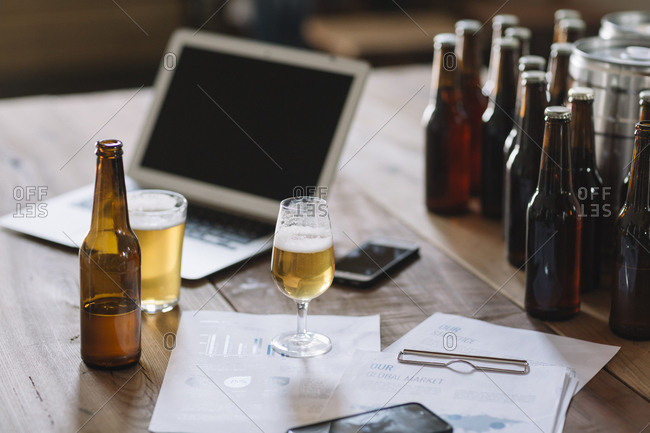 Beer bottles- glasses- documents and laptop on table
