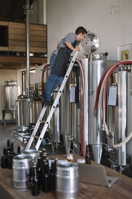 Young entrepreneur working at tank at a brewery