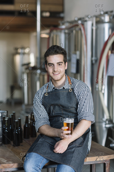 Portrait of smiling young man drinking a beer at a brewery