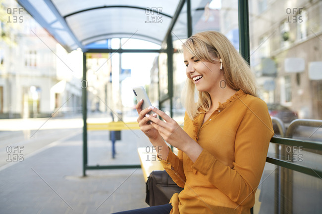 Happy young woman with wireless earphones using smartphone at bus stop