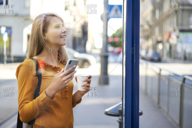 Smiling young woman with smartphone and takeaway coffee checking the schedule at bus stop