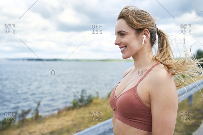 Portrait of smiling sporty woman with wireless earphones at the lakeside