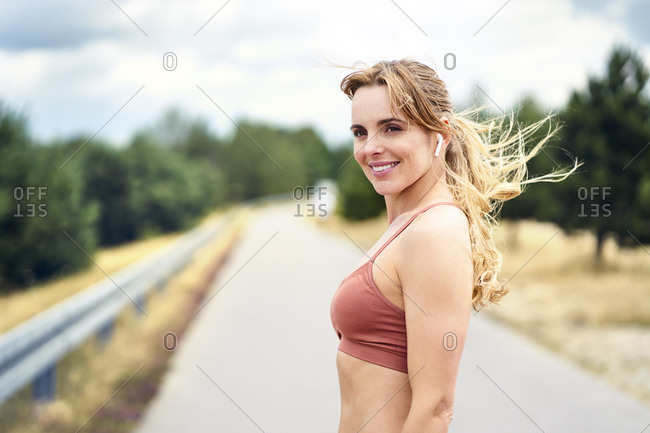 Portrait of smiling sporty woman with wireless earphones in nature