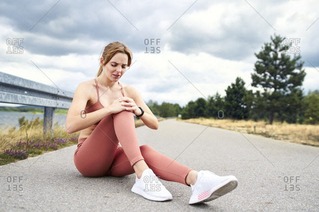 Woman sitting on ground and holding knee after injury during workout