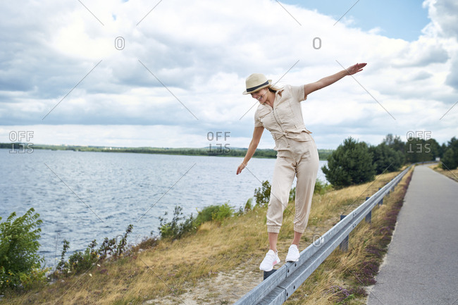 Happy woman balancing on crash barrier at the lakeside