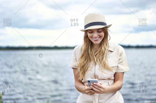 Happy woman checking cell phone at the lakeside