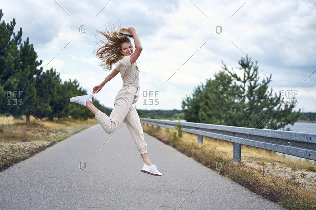 Cheerful woman jumping on rural road