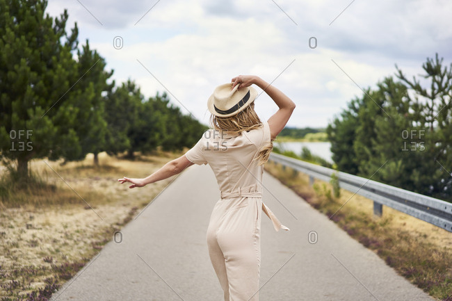 Rear view of woman with hat on a rural road