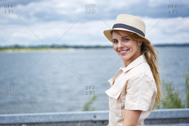 Portrait of smiling woman with hat at the lakeside